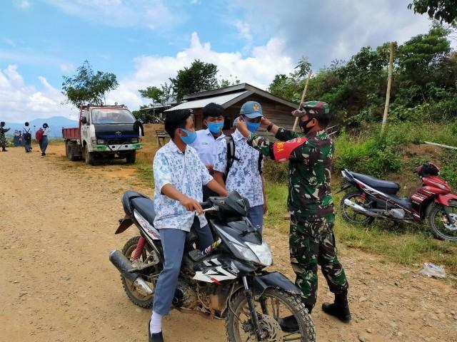 Aksi Peduli TNI-AD, Serda Hamka Berbagi Masker Agar Wilayahnya Aman Dari Virus Corona